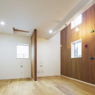 ボルダリングも楽しめる1階子ども室。将来は中央の壁に沿って仕切りを設け、2部屋にすることもできる。中央の壁の左上のハッチを開けてタラップを下ろすと、そこから中2階のロフトへ上がることができる