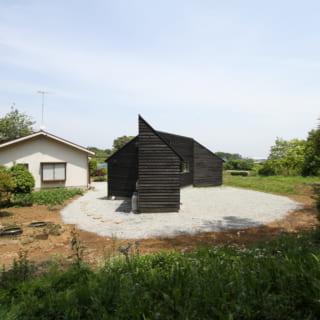 長細く、幅の違う建物を角度を変えて繋げた構造のSANNOMIYA。切妻屋根の向きも変化して、ひとつひとつが独立した小さな家のようにも見える。農地を宅地に変更した部分には砂利を敷いた。写真右側には畑が残っている