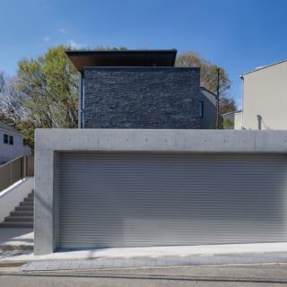 コンクリート壁のカーポートと天然石の外壁が印象的なファサード。上質なテクスチャーの外装素材と、窓が見えない「閉じた印象」が高級感を醸す
