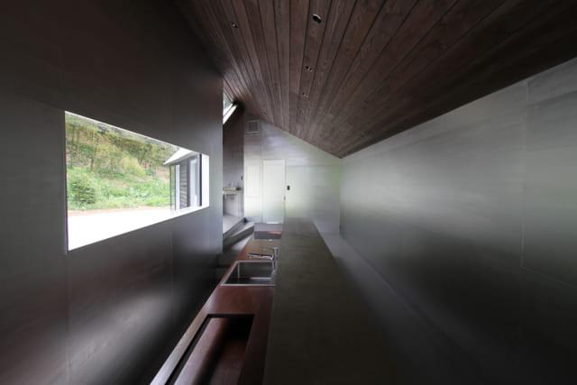 スッキリと長いワークトップが印象的なキッチン。室内に一体感を持たせるため、カウンターは床と同じコンクリートを使用した。大きく開口した窓から入った光は、メタリックシルバーの壁面に反射し室内をやさしく照らす。壁面にはところどころ山の緑も映り込み、空間に広がりを生む