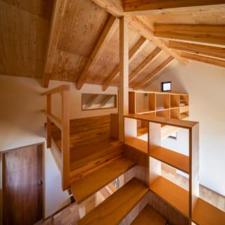 リビングの上のロフトスペース。木製フレームの棚は、収納・手すり・ベンチを兼ねるほか、風や光の通り道にも