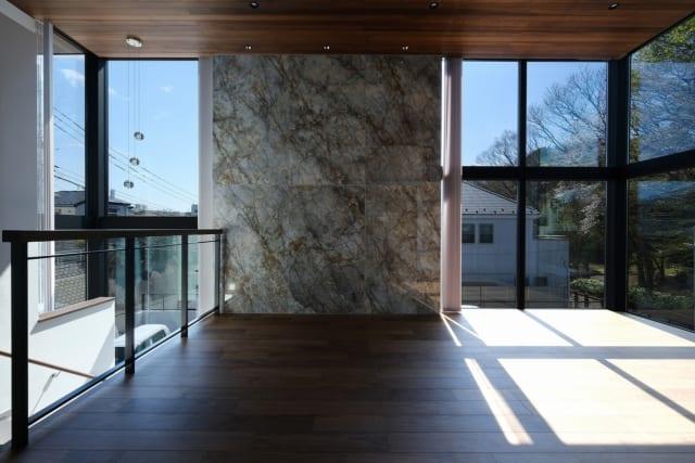 2階LDKで南を見る。LDKの南面、西面は、イタリア製の大判タイル壁の両脇に大きな窓を配したデザイン。部屋の隅が大きく開いているので視界が四方に広がり、開放感をいちだんと高めている。窓まわりには余計な壁がなく、屋外の景色が迫るように広がる