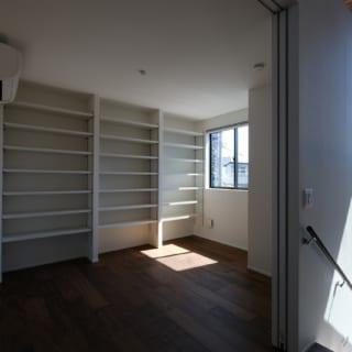 2階LDKの脇に配された子ども室。引き戸を開け放せばキッチンにいる奥さまからもお子さまの様子がわかる。南の明るい光が入る気持ちのよい空間には、大容量の本棚も