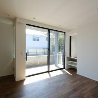 1階主寝室。南の掃き出し窓を挟むようにスリット窓と出窓を設けた。朝日から夕陽まで時間帯ごとの光が入り、風も通る。写真右手に行くと洗面・浴室。洗濯物は窓越しのバルコニーに干せるので家事動線は抜群。雨天時のことも考え、天井には室内物干しの器具も設置(写真左上)