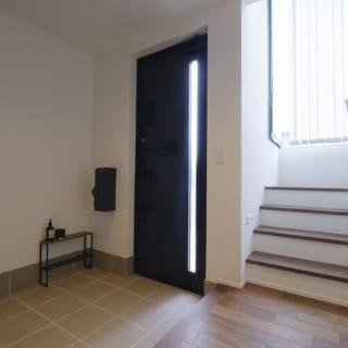 閉じた玄関土間(写真左)から吹抜けの階段に進むと、開放的な外の景色と上への広がりを感じられ、意外な展開に心が弾む。わずかな動線の中に仕掛けられた変化が楽しい