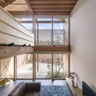 階段の途中から取ったリビング。1.5ⅿくらい外に張り出した家型のフレームのおかげで、冬は陽射しが入り、夏は陽射しが遮られるため、冷暖房負荷が少なくなっているそう