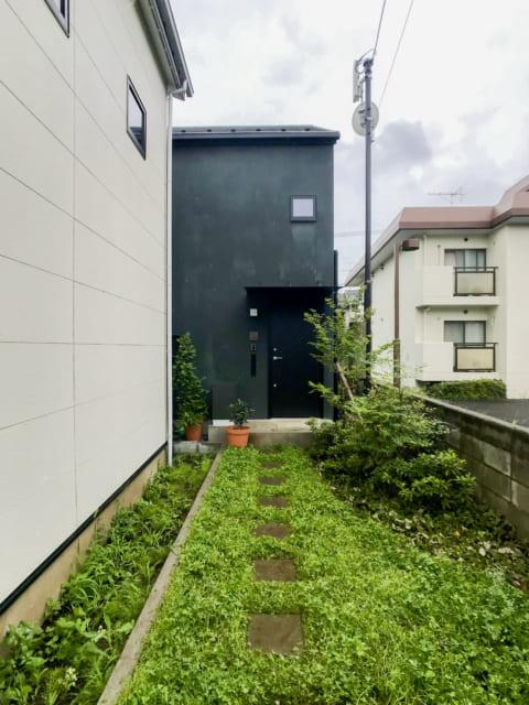 緑の絨毯を進んでいくO邸へのアプローチ。玄関にはOさんお手製の銅板の表札。