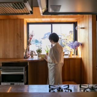 窓側には、Tさんのワークスペースにもなる広々カウンター。庇を設け、照明やダクトをキレイに収めた。絶妙な角度をつけることで陽光を室内に導く