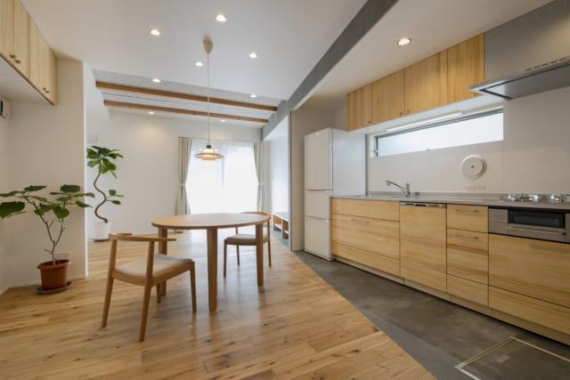 1階LDK。写真左のダイニング・リビングはオーク材、写真右のキッチンはモルタル調のフロアタイルと、床の素材を変えてさりげなくゾーニング。オーク材の床が奥に向かって斜めに広がる設計が奥行きや広がりを強調し、開放感をいちだんと高めている
