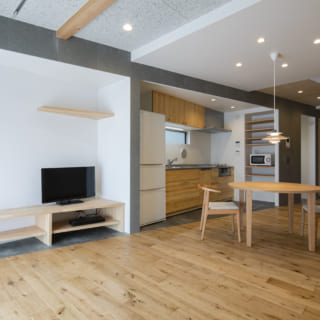 リビングからLDKを見る。オーク材の床の部分が南(写真左)に向かって広くなり、空間の広がりを強調。テレビ台も斜めラインに合わせて造作している。リビングスペースの天井は表情豊かな木毛セメント。仕切り壁はないが、天井や床の素材でそれとなくスペースを分けている