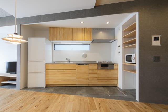 収納豊富な1階キッチン。横長のハイサイド窓で明るさも十分だ。写真右手には、トイレ&手洗い、書斎、玄関が続く。トイレや書斎の空間ボリュームのおかげで玄関からはこのキッチンが視界に入らず、生活感を見せずにすむ