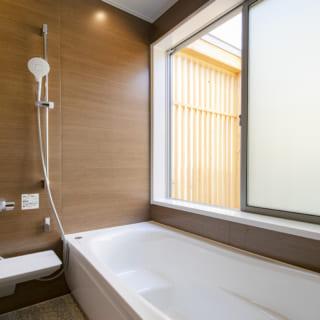 2階バスルーム。窓越しの縦格子に囲われたスペースの下にはモミジがあり、成長すれば緑を眺めて入浴できる