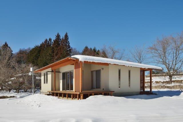 雪の中に佇むCさん邸。玄関脇のヒノキの柱は、Cさん自らの手で伐採したもの。