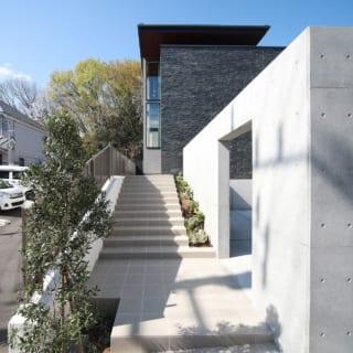 タイル敷のアプローチ階段をのぼって玄関へ向かうと、コンクリート壁のカーポートの先に天然石の外壁と木板張りの大きな軒が見えてくる。邸内に入るまでに質感の異なる素材が連続していく「道行きの楽しみ」も、M邸の魅力