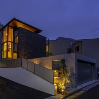 外観夕景。明かりが灯ると1階から2階まで連続するコーナー窓が引き立ち、住宅とは思えない洒落た表情を見せる