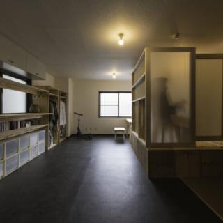 キッチンから室内を見る。写真左側には設計料無料のスタンダード家具を壁面収納として並べている。高さや奥行きが揃っていて見た目がよく、造作家具のよう。写真右側はノビルームの間仕切りを出して囲った状態。ワンルームの大空間でも独立感を得られ、リモートワークに最適