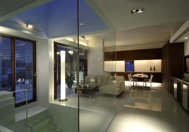 3階LDK。間接照明、大判の白タイル、脚にアクリルを使った浮遊感のある家具が洗練を極め、高級ホテルの一室を彷彿とさせる。手前のガラス張り部分が開閉式トップライトと吹抜けの階段室。強化ガラスで囲うことで全ての方位の光を通しつつ、吹抜けによる冬の寒さを防いでいる