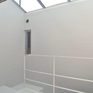 2階への階段を上がったところ。上部にはトップライトがあり、室内階段も明るい。賃貸住戸専用の門扉やこの室内階段は入居者さましか使わないため、戸建てのようなプライベート感がある