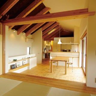 寝室を除く生活空間は2階に集めた。天井が高く、開放感たっぷりの空間は1階の天井を下げ2階の天井の片面は梁を見せたことで実現した。和室とダイニングを仕切る引き戸は左の壁面に全て引き込める。引き戸を閉めても梁から上が開いているため2階全体が広く感じられ圧迫感がない