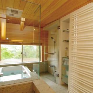 2階浴室。壁面は木材、床面は石材とナチュラルな素材を組み合わせリラックスできる空間に。窓は道路に面しているため、下から浴室内が見えないよう、窓枠の下ラインに合わせて縁側のようにフラットな面を設けた。天気がいい日は浴室から富士山も楽しめる