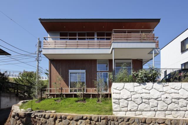 南の外観。海側の南面には大開口とテラスを設け、外壁はシルバーのガルバリウム鋼板と杉板で明るい色調に。敷地は2段擁壁だったが1段だけ残し、隣地とつながる部分に安全性を高めた新しい擁壁を造成(写真右)。残りは斜面にして緑を植え(写真左)、周囲の景観に馴染ませた
