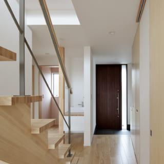 階段付近から玄関を見る。玄関の横(写真左奥)には、客間や書斎などに使えるフリースペースとトイレがある