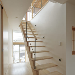 玄関を入るとスケルトン階段が。その先には窓があり、家々の合間に見え隠れする海を感じながら2階へのぼる