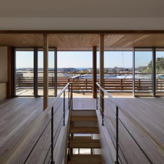 階段をのぼりきって2階に上がると開放感あふれるパノラマビューが現れ、心が弾む。連続窓の先には、鎌倉の町並みと水平線が広がる贅沢な眺め。工藤さんは窓際の天井をあえて低めに設計し、横に広がるパノラマ感を高めている