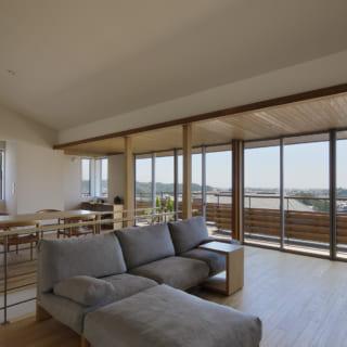 2階LDKの天井は、連続窓のある南に向かって低くなる勾配天井。海を望む南の天井高をあえて抑えたことで横の広がりが際立ち、景色のパノラマ感がアップ