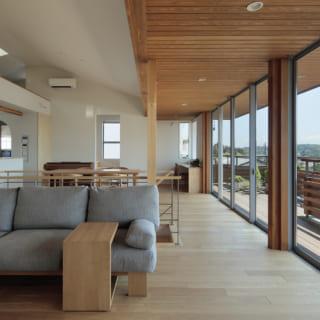 2階LDKのリビングからダイニング方向を見る。南一面(写真右)は壁を切り取ったような連続窓の大開口で、抜群の開放感。窓際の天井はテラスの軒裏の杉板をそのまま引き込んだ。一直線に続く杉板天井が横の広がりを強調し、展望廊下のような雰囲気もある