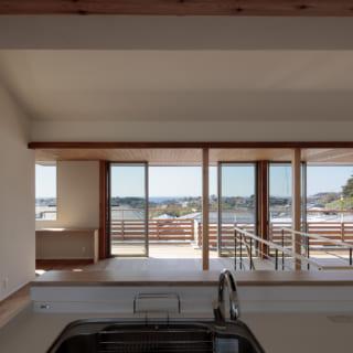 2階LDKのキッチンからダイニング、テラスを見る。のびやかな海と町の景色を眺めながら料理ができる