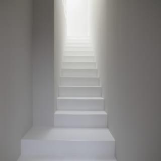 玄関を開けると賃貸住戸2階への室内階段。階段上部にはトップライトがあり、南側の明るい光が落ちてくる