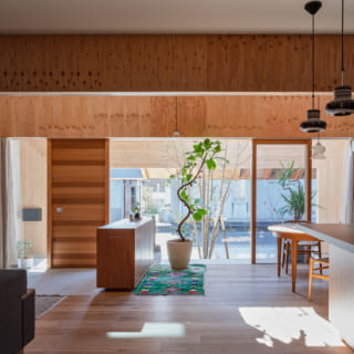 リビングスペースから前庭を見る。邸内~前庭~生活道路~お向かいの住宅の外壁までが1つの大空間のように感じられる設計が、のびやかな開放感を創出。写真右のキッチンはオリジナル。木材とモルタルを使った洒落たデザインで、インテリアに馴染んでいる
