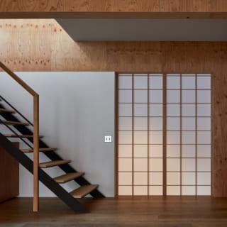 LDKの奥には2階への階段が。一般的に、こうした鉄骨階段はササラ(階段の側面)を最後に垂直に曲げて床におろすが、川本さんは直線で伸ばして床に設置させている。また手すりは垂直部を床から少し浮かすなど、さりげないこだわりで美しいオブジェのような階段に仕上げた