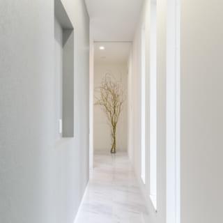 玄関からリビングに続く廊下も、ホテルの廊下の雰囲気を重視した。優しいグレーの壁面が場の印象を和らげる