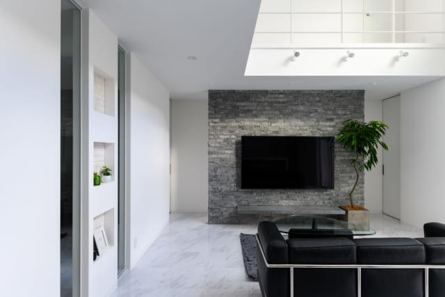 1階リビング。床暖房を配し、大理石風のPタイルから受ける印象とは違い冬も温かな空間。吹き抜けのおかげで開放感があるのに加え、リビング裏の廊下や、画像右壁面の裏にある水回りまで視線が抜け空間をより広く認識できる。視線の抜けは、家族の気配を感じるためにも重要