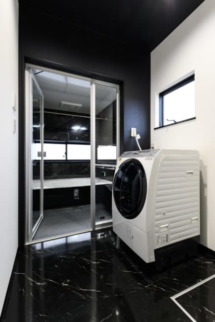 1階脱衣室から浴室を見る。黒が多めのモノトーンでシックな印象
