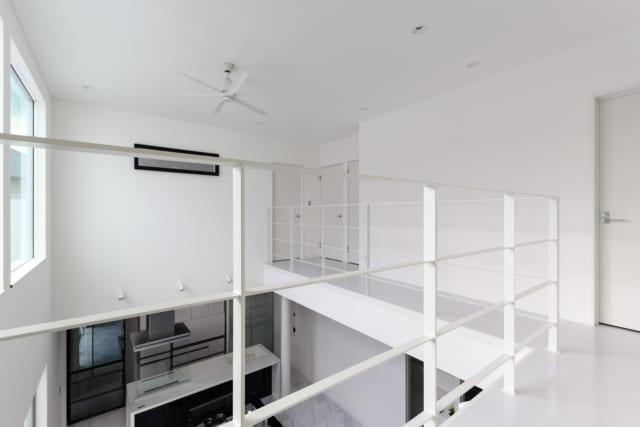 2階、東側の廊下から見たところ。1階に見えるのはキッチン。奥様の「キッチンから室内が見渡せるように」というご要望が反映されているのがわかる。写真奥、黒枠の窓は寝室の窓。「空間につながりを持たせるためにも、家の内側に向かった窓をたくさんつけました」と桑名さん