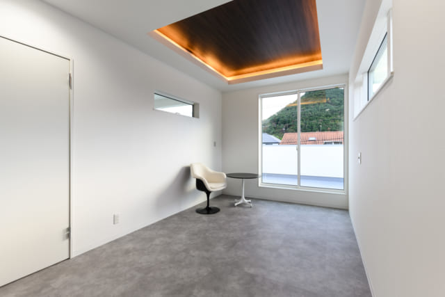 2階寝室は、ほぼ眠るためだけに使用。横になったとき照明の光が目に直接入らないよう、折り上げ天井にし、間接照明を設けた。床も落ち着いた色味に床は落ち着いた色味に。ほか、写真左のドア手前、掃き出し窓に相対する壁はダークブラウンで仕上げている