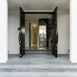 玄関から屋内を見る。2階に上がる螺旋階段はT様のこだわりのひとつ。玄関の正面に窓があるため、家の向こう側まで視線が抜け、空間が広く感じられる