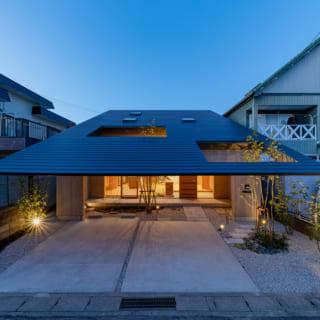 道路から見たY邸。道路側には駐車スペースと前庭があり、住宅は大胆にセットバック。ゆったりとした余裕を感じさせる佇まいとなった。住まいを守るように覆う大きな屋根は軒も深く、手前には2つの大きな開口。建築としてのデザイン性が高く、しばし見とれてしまうファサードだ