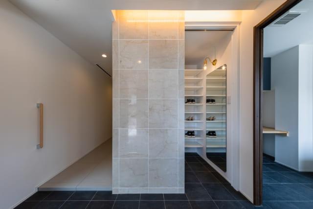 大理石を用いたモダンな作りの玄関。扉付のシューズインクローゼット。玄関周りに靴を置く必要がなく、すっきりと見せられる