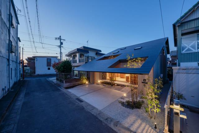 前面の生活道路は、Y邸の南側に位置する。道路を挟んだ向かいに立つのは3階建ての住宅(写真左)。Y邸の大開口があるのは1階LDKの道路側。邸内から見ると、連続する門型フレームとゆったりと伸びた深い軒の効果で、お向かいの家の外壁までが1つの空間にように感じられる