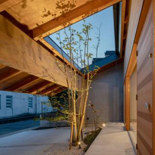 玄関前から軒下を見る。軒の開口部の下にあるのが、最も道路に近い門型フレーム。軒は外壁から5.4m、開口部の先は片持ちで2.7m出ている難度の高い造りだが、川本さんは構造を試行錯誤して先端の支柱を設けないデザインを実現。洗練されたダイナミックな美しさを生み出した