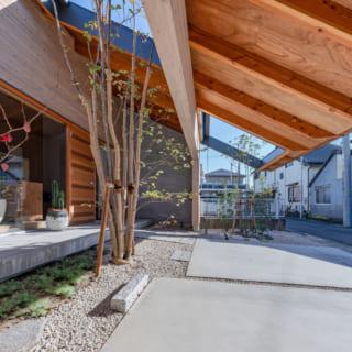 LDK前から軒下を見る。油分が多く劣化しにくい屋久島杉を使った板張りの外壁も、家を支える門型フレームの1つ。大きな軒は、夏場の日よけや雨天時の雨よけとして大活躍。軒に覆われていることで前庭のプライベート感も増し、気兼ねなくBBQなどを楽しめる