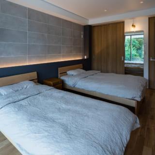 ホテルのゲストルームのようなTさんご夫婦のベッドルーム。姿見に庭の緑が映るよう工夫されている