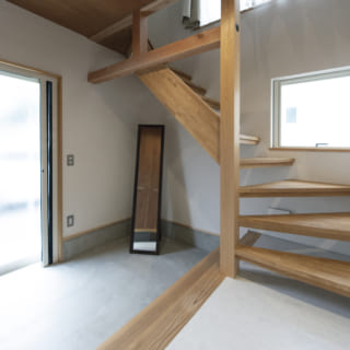 自邸玄関。広い土間から邸内へ入ると2階への階段がある。階段沿いの大きな窓からは明るい光が降りそそぐ