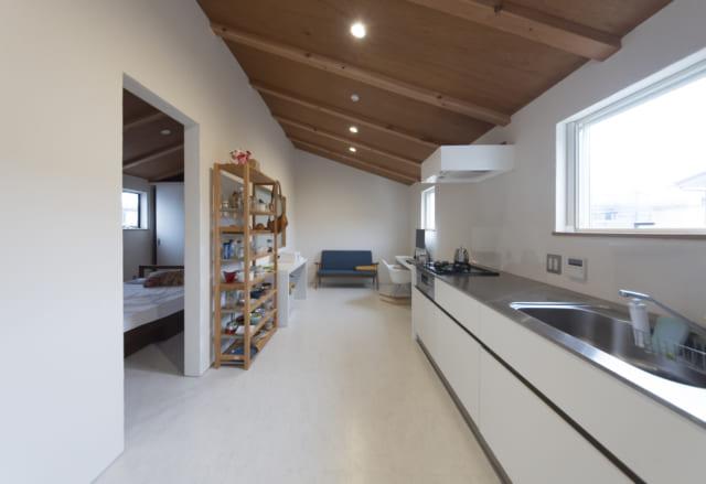 自邸2階のLDKはL字型。L字の一辺がリビング、もう一辺が東(写真右)から爽やかな光が入るキッチンと、ご主人のための仕事スペース(写真奥)。仕事スペースにはソファも置いてあり、ご主人と奥さまが仕事の合間に会話を楽しむ場所にもなっている。写真左側は寝室