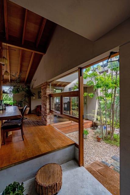 中庭が玄関までのアプローチや縁側の役割も果たす。土間のように仕上げた玄関には、家族で伐採した木を踏み台として利用