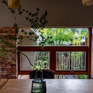 キッチンで作業しながら、中庭の様子もうかがえる大きな窓。レンガタイルのアクセントウォールも落ち着きをもたらしている